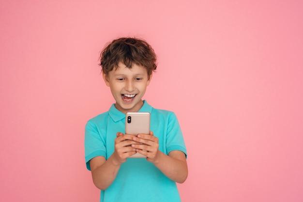 Vrolijke jongen gekleed in een poloshirt, met een smartphone op een roze.