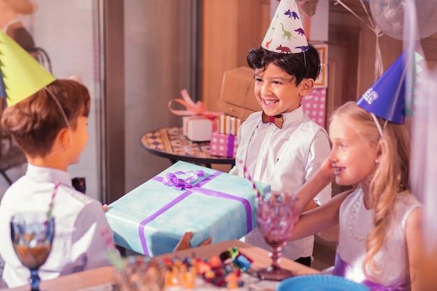 Vrolijke jongen glimlacht en draagt een feestmuts terwijl hij cadeau geeft aan zijn vriend
