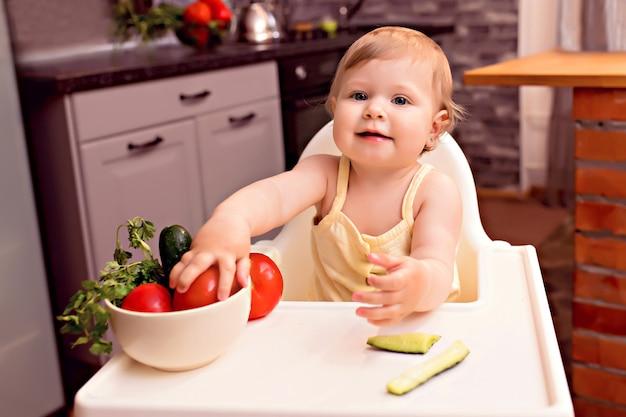 Vrolijke jongen groenten eten. portret van een gelukkig meisje in een kinderstoel in de keuken