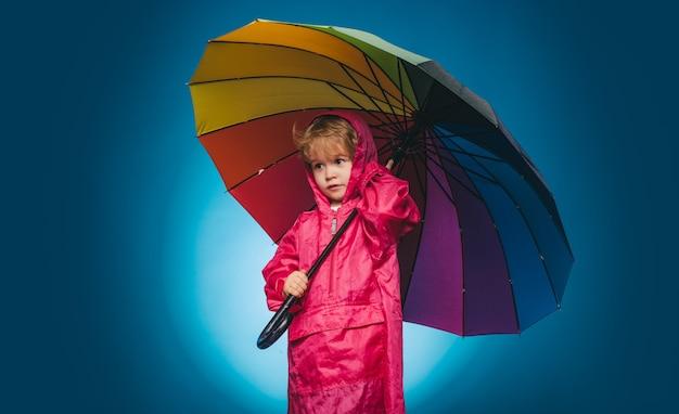 Vrolijke jongen in regenjas met kleurrijke paraplu.