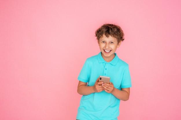 Vrolijke jongen met golvend haar, met een smartphone op een roze.