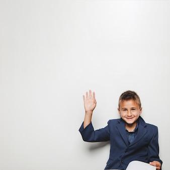 Vrolijke jongen met hand omhoog