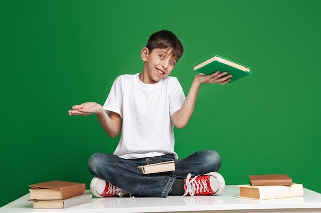 Vrolijke jongen met sproeten die tussen boek en lege copyspace kiest terwijl hij naar de voorkant over de groene muur kijkt