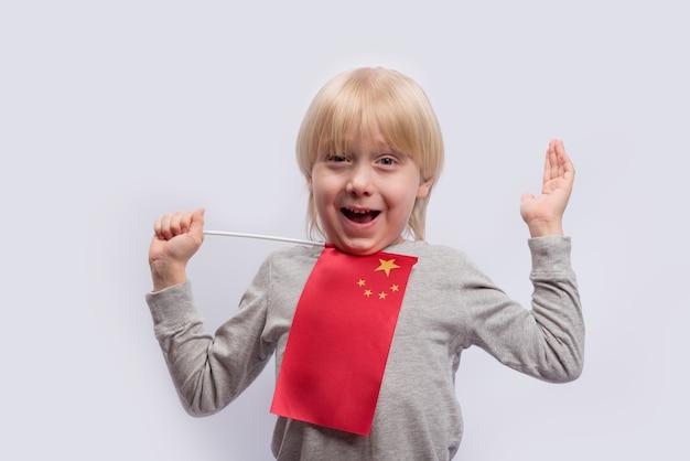 Vrolijke jongen met vlag van china op witte achtergrond. chinees leren voor kinderen.