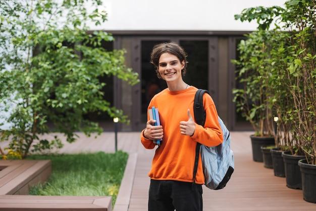 Vrolijke jongen permanent met rugzak en boeken in de hand en gelukkig grote duim opdagen op de binnenplaats van de universiteit
