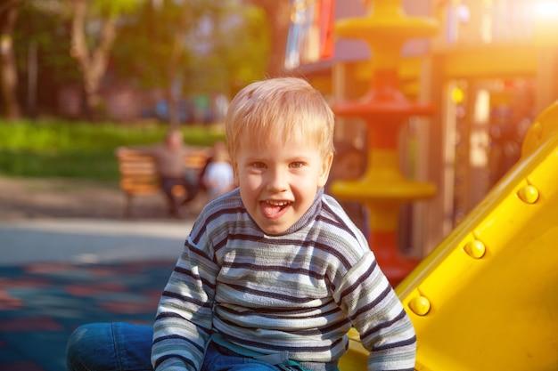 Vrolijke jongen spelen op de speelplaats