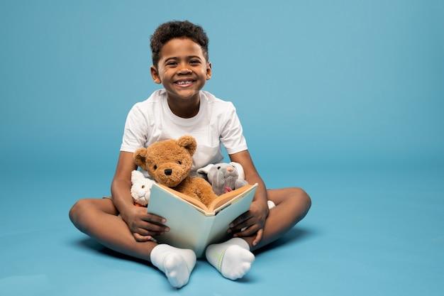 Vrolijke jongen van elementaire leeftijd met brede glimlach zittend op de vloer in de studio, boek lezen en spelen met zacht speelgoed