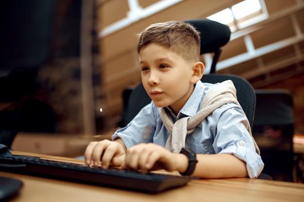 Vrolijke jongen werkt op pc, kleine blogger. kid bloggen in thuisstudio, sociale media voor jong publiek, online internetuitzending, creatieve hobby