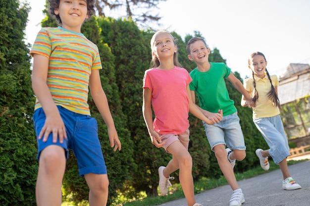 Vrolijke jongens en meisjes springen met opgeheven been