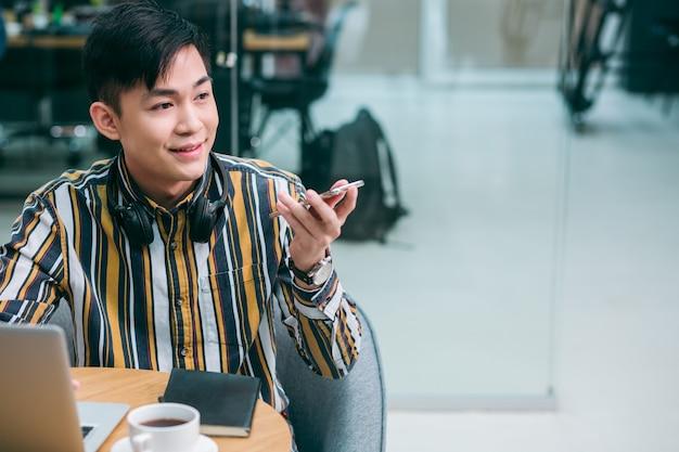 Vrolijke jongere die virtuele assistentie gebruikt op zijn smartphone en spraakopdrachten geeft. websitebanner