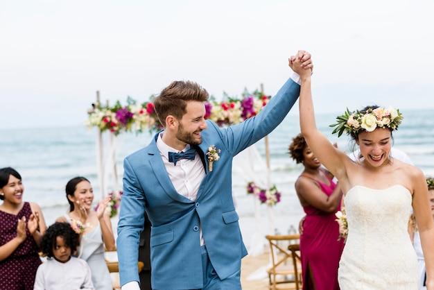 Vrolijke jonggehuwden bij strandhuwelijk ceremnoy