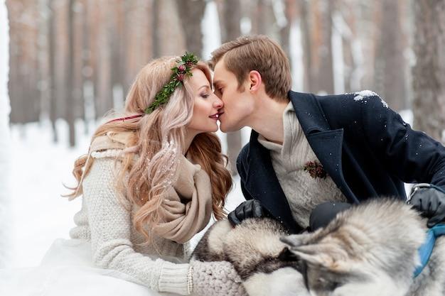 Vrolijke jonggehuwden kussen op achtergrond van husky. winter bruiloft. kopieer ruimte