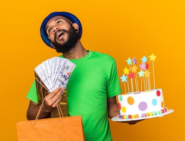 Vrolijke, kantelende jonge afro-amerikaanse man met een feestmuts met geschenken en cake met contant geld