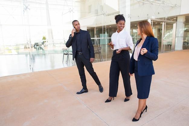 Vrolijke kantoorcollega's lopen over lobby en chatten