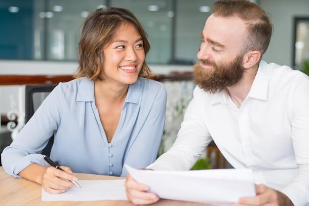 Vrolijke kantoormedewerkers flirten en een grapje maken