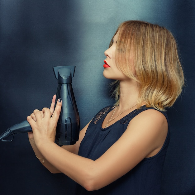 Vrolijke kapper, vrouw poseren met een föhn in haar handen