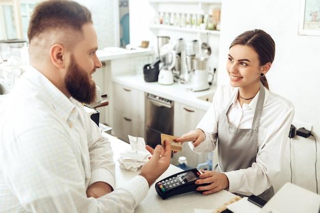 Vrolijke kassier die digitaal apparaat voor betaling gebruikt