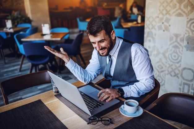 Vrolijke kaukasische bebaarde knappe zakenman zitten in café en met behulp van laptop. op tafel staan laptop, koffie, bril en water.