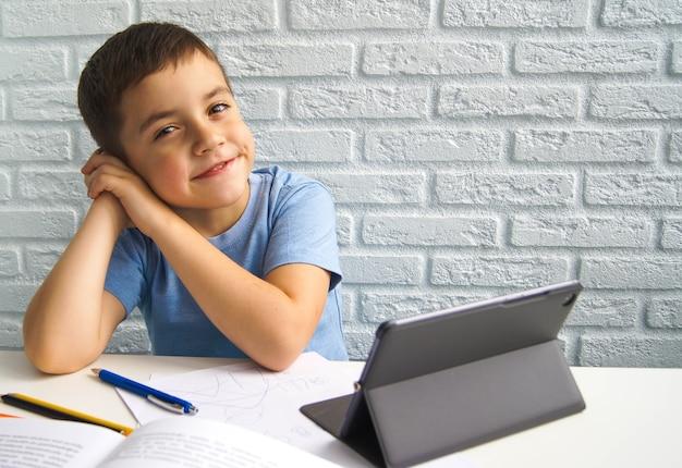 Vrolijke kaukasische kindjongen die laptop met behulp van. thuisonderwijs, leren op afstand, online onderwijs