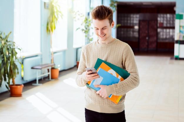 Vrolijke kaukasische student met smartphone en cursusboeken die zich in campus van universiteit bevinden die met zijn vrienden via sociale media in zonnige dag texting