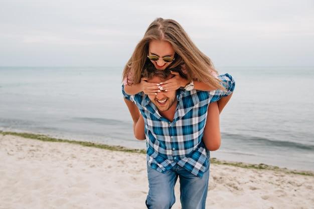 Vrolijke kerel die haar meisje achter de rug houdt, terwijl zij zijn ogen behandelt door handen