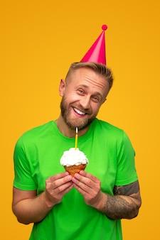 Vrolijke kerel die in glb verjaardag cupcake houdt