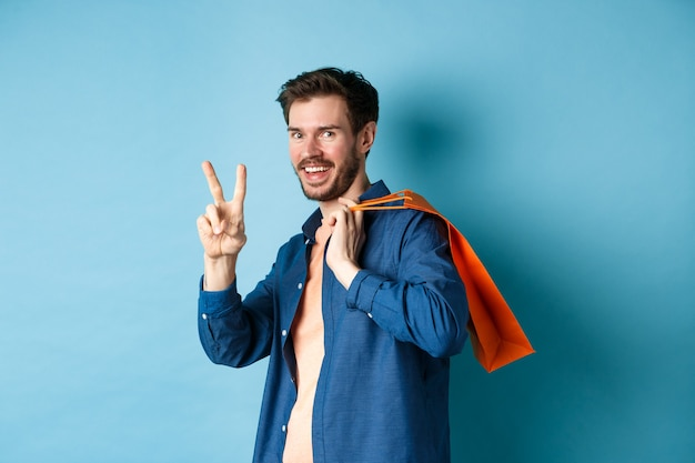 Vrolijke kerel die oranje boodschappentas op schouder houdt, glimlachend en vredesteken toont, die zich op blauwe achtergrond bevindt. kopieer ruimte
