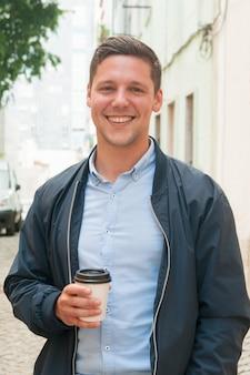 Vrolijke kerel die van openluchtkoffiepauze geniet