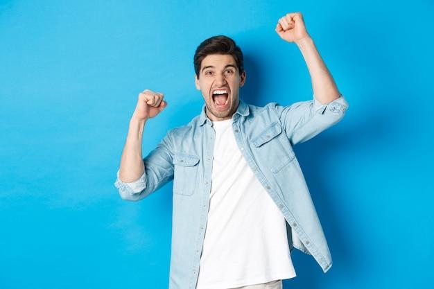 Vrolijke kerel die vuistpompen maakt en voor iemand wroet, schreeuwt van vreugde, triomfeert over overwinning, staande tegen een blauwe achtergrond