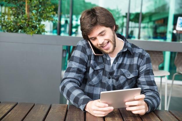 Vrolijke kerel het letten op video op het gadgetscherm