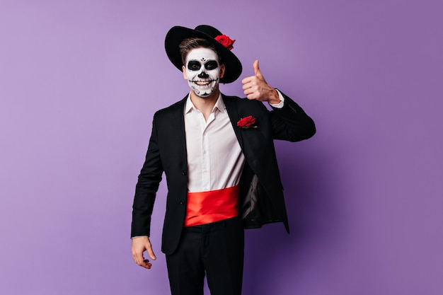 Vrolijke kerel in goed humeur verschijnt duim, poseren in kostuum voor feest op halloween.