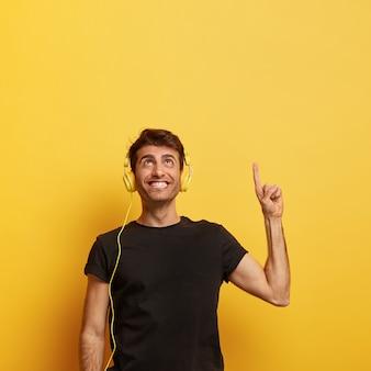 Vrolijke kerel met brede glimlach, wijsvinger wijst, luistert naar muziek in de koptelefoon, geniet van goed geluid