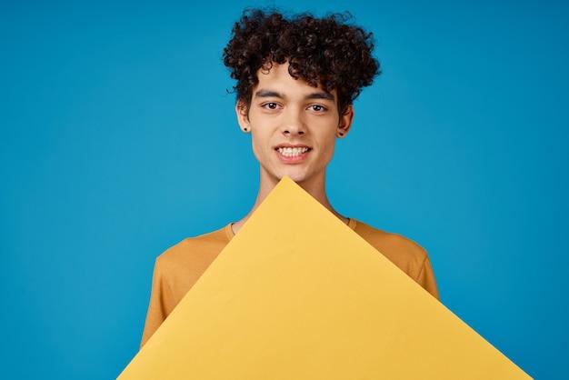 Vrolijke kerel met krullend haar van gele asters in zijn handen studioblauw