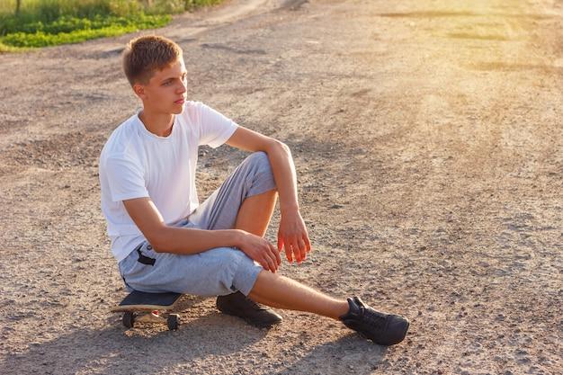 Vrolijke kerel zittend op een skateboard op de weg op een zonnige dag