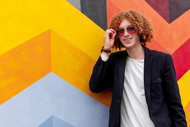 Vrolijke kerel zonnebril in de buurt van kleurrijke muur aanpassen