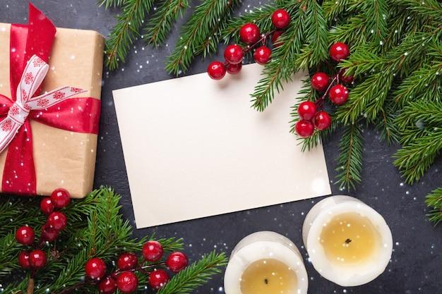 Vrolijke kerstkaart met papier, geschenkdoos, kaarsen en fir tree branch op zwarte achtergrond.