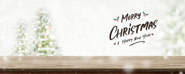 Vrolijke kerstmis en gelukkig nieuwjaar op houten tafelblad bij vervagen bokeh kerstboom met string licht