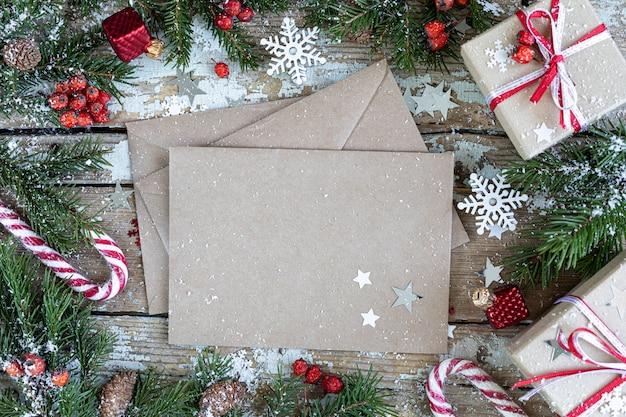 Vrolijke kerstmis en gelukkige vakantie wenskaart, frame, banner. nieuwjaar. nieuwjaarskaart met sneeuw op houten achtergrond. winter xmas vakantie thema. plat leggen. kopieer ruimte