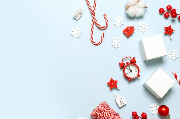 Vrolijke kerstmis en nieuwjaar felicitatie kaart met papieren dozen, rode klok, glitter vervagen, auto speelgoed, sterren en rode bessen op blauwe achtergrond