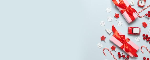 Vrolijke kerstmis en nieuwjaar felicitatie kaart met roze papieren dozen, rode linten, glitter vervagen, auto speelgoed, sterren en rode bessen op blauwe achtergrond