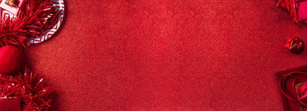Vrolijke kerstmis en nieuwjaar rode achtergrond bovenaanzicht van klatergoud, cadeau, bal, lint versieren op tafel