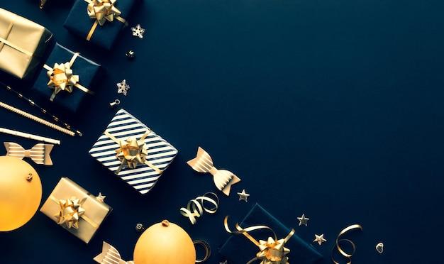 Vrolijke kerstmis, kerstmis en nieuwjaarsvieringsconcepten met giftdoos en ornament in gouden kleur op donkere achtergrond. winterseizoen en jubileumdag
