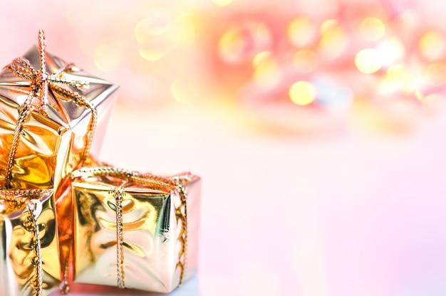Vrolijke kerstmis, nieuwjaar, geschenken in gouden dozen op een achtergrond van roze en gele bokeh.