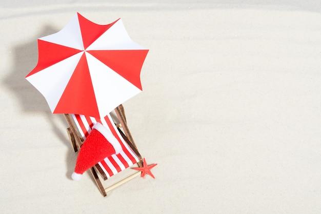 Vrolijke kerstmis op strandconcept. lounge stoel met paraplu en kerstmuts. bovenaanzicht