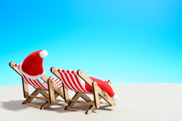 Vrolijke kerstmis op strandconcept. twee ligstoelen met kerstmutsen