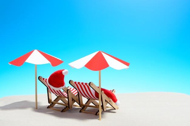 Vrolijke kerstmis op strandconcept. twee ligstoelen met parasols en kerstmutsen