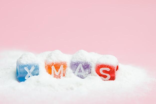 Vrolijke kerstmis van woorden die van kleurrijke brievenblokken wordt gemaakt op witte sneeuw en roze