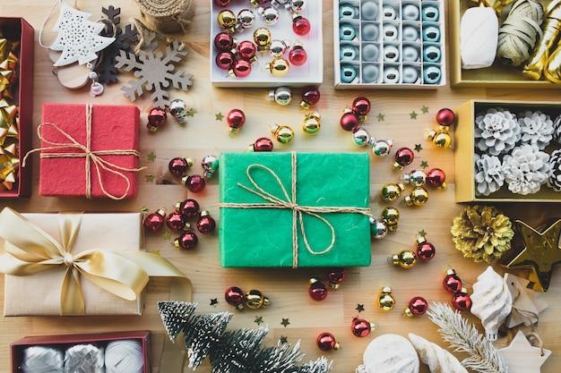 Vrolijke kerstmisconcepten met aanwezige giftdoos en ornamentelement op hout