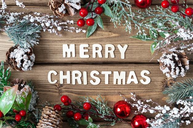 Vrolijke kerstsamenstelling dennentakken met kegelbessen en sneeuwversieringen op oude donkere houten