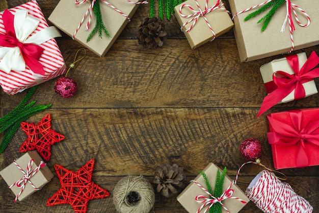 Vrolijke kerstversiering. plat lag essentiële verschil objecten geschenkdoos & fir tree op houten bord